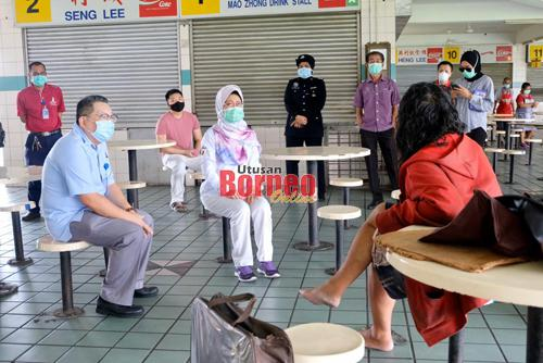 Fatimah memujuk seorang gelandangan untuk dipindahkan ke Anjung Singgah buat sementara sehingga PKP dimansuhkan. - Gambar oleh Muhammad Rais Sanusi